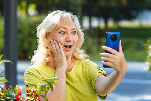 Starsza kobieta rozmawia ze zdziwieniem przez telefon przez łącze wideo