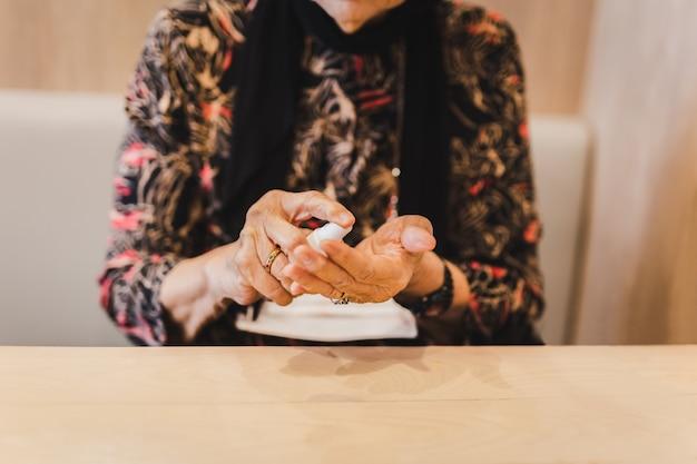 Starsza kobieta rozpyla środek dezynfekujący alkoholem na dłoniach.