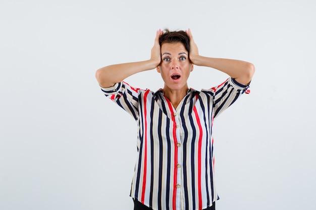 Starsza kobieta, ściskająca głowę rękami, trzymająca usta w koszuli w paski i wyglądająca na zaskoczoną, widok z przodu.