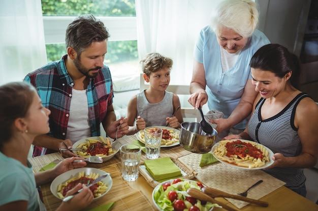 Starsza kobieta serwująca posiłek swojej rodzinie