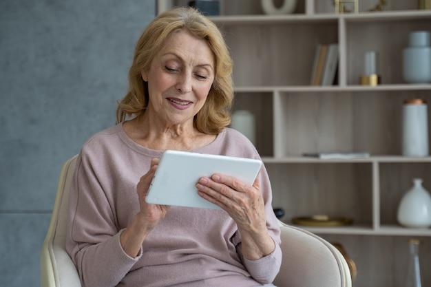 Starsza kobieta siedząca w fotelu i korzystająca z cyfrowego tabletu, siedząca na fotelu w niej
