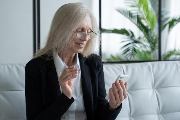 Starsza kobieta siedzi na kanapie i uśmiecha się podczas korzystania z telefonu, świętując sukces