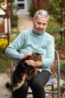 Starsza kobieta siedzi na krześle i pieści kota