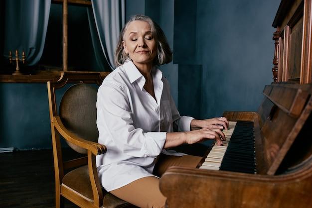 Starsza kobieta siedzi na krześle w pobliżu występu muzyki fortepianowej