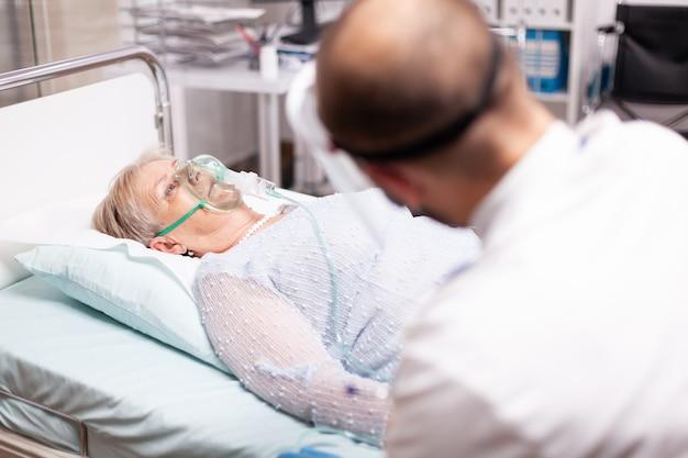 Starsza kobieta siedzi na łóżku kliniki z maską tlenową w czasie covid19