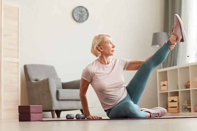 Starsza kobieta siedzi na podłodze i wyciąga nogę podczas treningu sportowego w salonie w domu