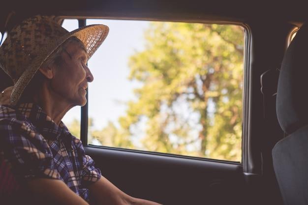 Starsza kobieta siedzi na tylnym siedzeniu w samochodzie i zagląda w okna into