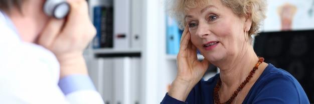 Starsza kobieta siedzi na wizycie u lekarza i skarży się na ból głowy. mężczyzna lekarz mierzy ciśnienie krwi pacjenta w klinice.