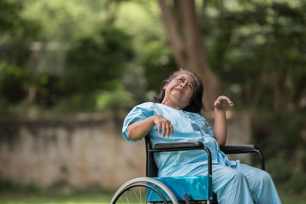 Starsza kobieta siedzi na wózku inwalidzkim z chorobą alzheimera