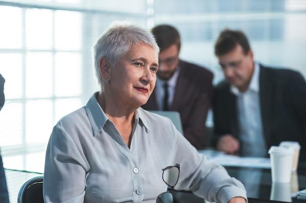 Starsza kobieta siedzi przed biurkiem