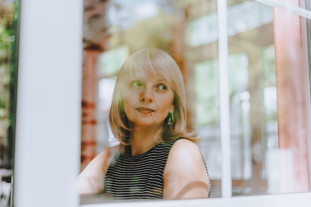 Starsza kobieta siedzi przed oknem dojrzała dorosła kobieta patrząca smutno i zamyślona zdrowie psychiczne