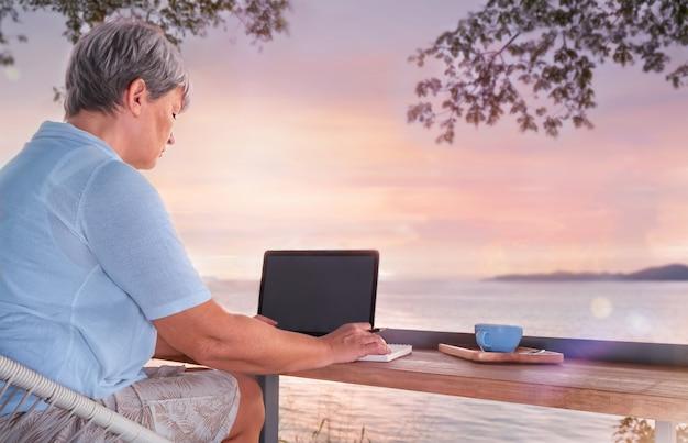 Starsza kobieta siedzi w kawiarni z widokiem na morze i pracuje jako freelancer