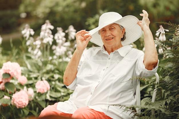 Starsza kobieta siedzi w parku. babcia w białym kapeluszu.