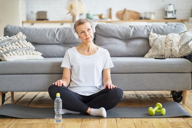Starsza kobieta siedzi ze skrzyżowanymi nogami w słuchawkach, słucha muzyki w salonie, relaksuje się po ćwiczeniach