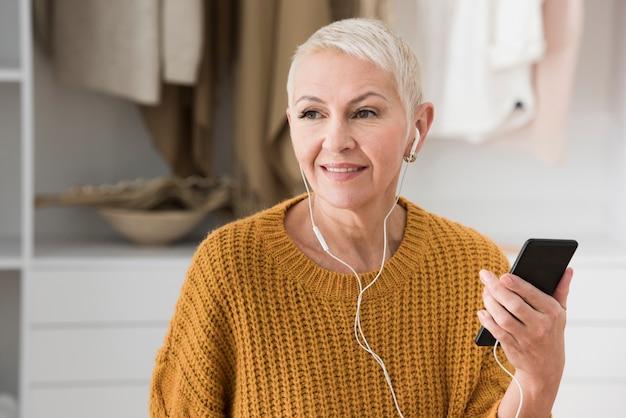 Starsza kobieta słucha muzyka na hełmofonach i trzyma smartphone