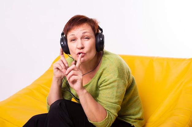 Starsza kobieta słucha muzykę i robi cii znakowi