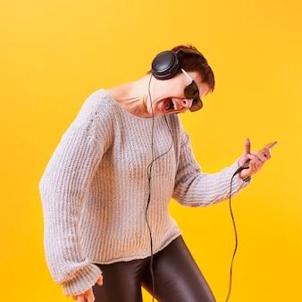 Starsza kobieta słucha muzykę rockową