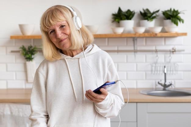 Starsza kobieta słucha muzyki na słuchawkach w domu