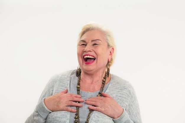 Starsza kobieta śmiejąca się na białym tle wesoła starsza pani