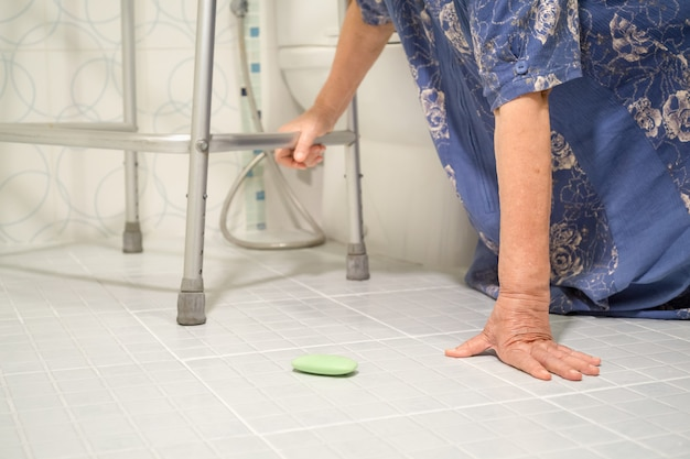 Starsza kobieta spada w łazience, ponieważ śliskie powierzchnie