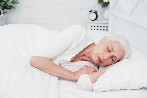Starsza kobieta śpi na białym łóżku