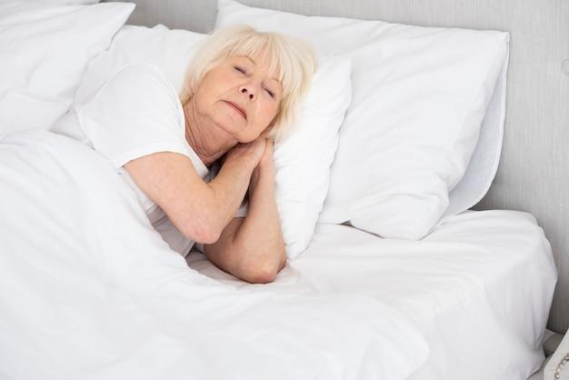 Starsza kobieta śpi w swoim łóżku
