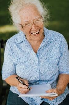 Starsza kobieta spisywać jej wspomnienia w notatniku
