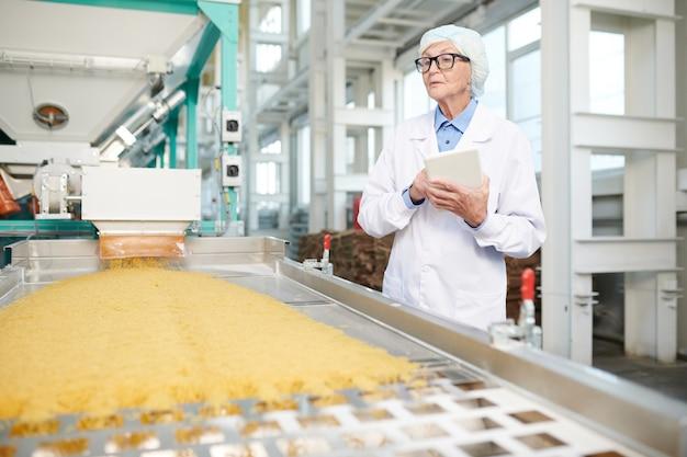 Starsza kobieta sprawdza produkcję