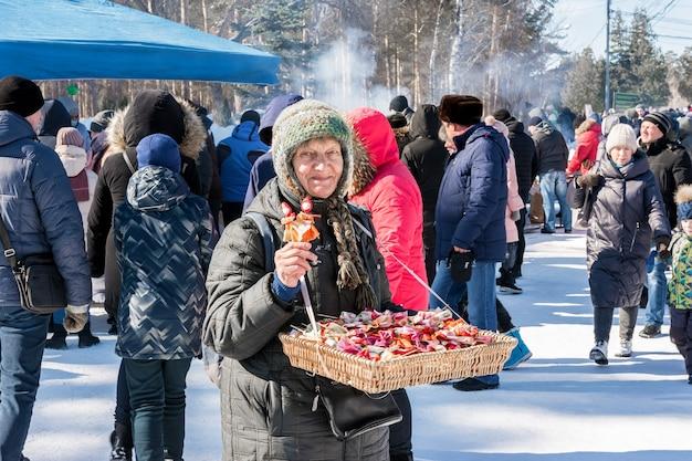 Starsza kobieta sprzedaje ręcznie robione pamiątki na festiwalu maslenitsa