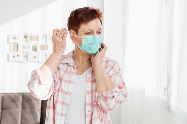 Starsza kobieta stawia na medyczną maskę w domu