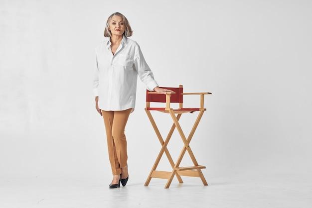 Starsza kobieta stoi w pobliżu krzesła styl życia biała koszula pozuje