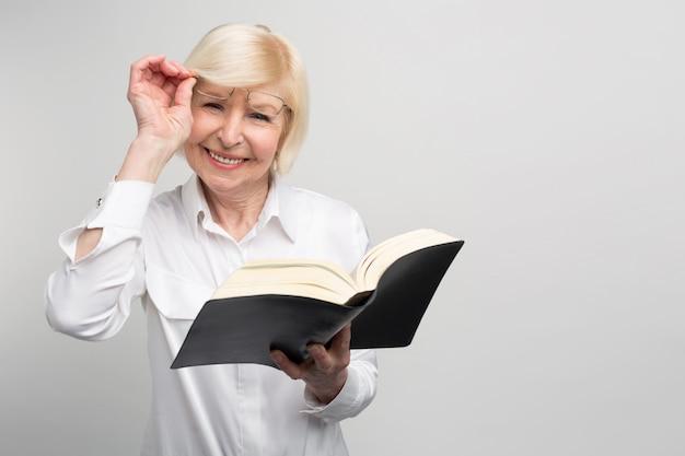 Starsza kobieta stoi w pokoju i czyta książkę. stara się nauczyć czegoś nowego na emeryturze, ponieważ ma tam dużo wolnego czasu.