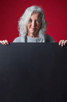 Starsza kobieta stoi za pustym czarnym afiszem na czerwonym tle