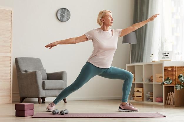 Starsza kobieta stojąca na macie do ćwiczeń i robi joga w salonie w domu