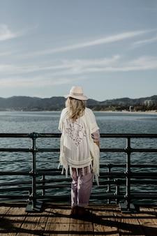 Starsza kobieta stojąca przy molo