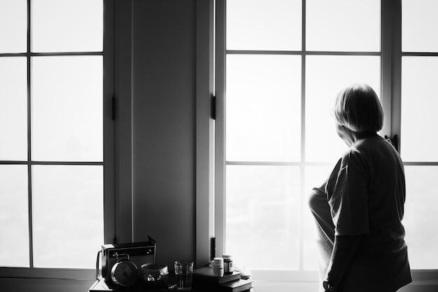 Starsza kobieta stojąca samotnie w domu