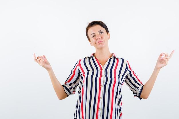 Starsza kobieta stojąca w medytacyjnej pozie, mrugająca w pasiastej bluzce i wyglądająca optymistycznie. przedni widok.