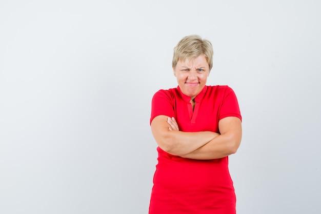 Starsza kobieta stojąca ze skrzyżowanymi rękami w czerwonej koszulce i uparty patrząc.