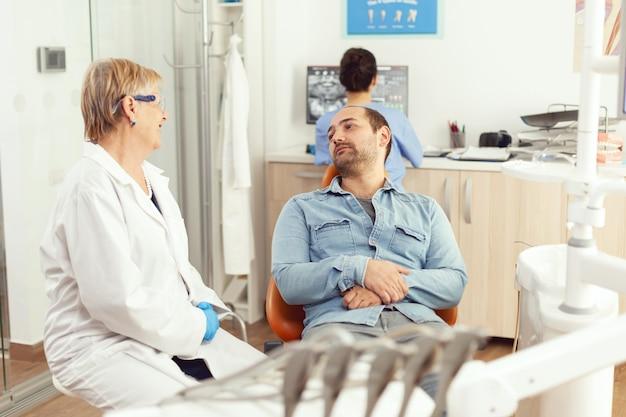 Starsza kobieta stomatolog rozmawia z pacjentem o leczeniu bólu zęba podczas konsultacji stomatologicznej w gabinecie stomatologicznym