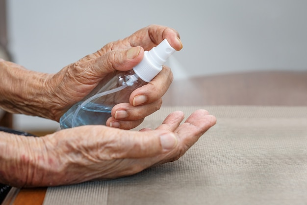 Starsza kobieta stosuje alkoholowe dłonie do czyszczenia rąk w celu ochrony przed koronawirusem covid-19