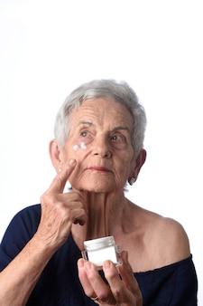 Starsza kobieta stosuje skóry śmietankę lub moisturizer jej twarz