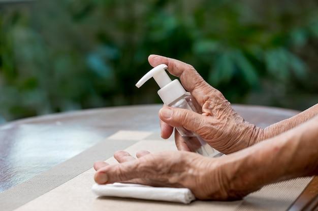 Starsza kobieta stosuje żel do czyszczenia rąk w żelu alkoholowym, aby pomóc chronić przed koronawirusem covid-19