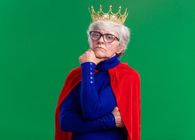 Starsza kobieta superbohaterka ubrana w czerwoną pelerynę i okulary z koroną na głowie patrzącą na bok