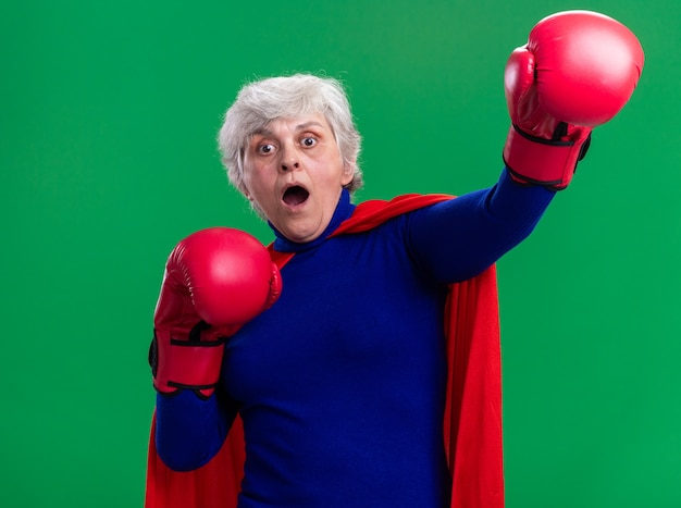 Starsza kobieta superbohaterka ubrana w czerwoną pelerynę i rękawice bokserskie, patrząca na kamerę przestraszona i zmartwiona, stojąca na zielonym tle