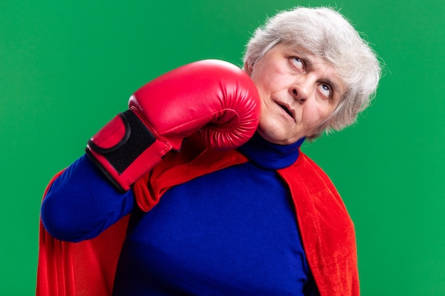 Starsza kobieta superbohaterka ubrana w czerwoną pelerynę z rękawicami bokserskimi uderzająca się w siebie stojąc na zielonym tle