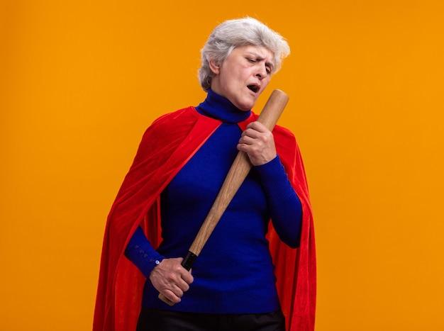 Starsza kobieta superbohaterka w czerwonej pelerynie trzyma kij bejsbolowy, używając go jako mikrofonu