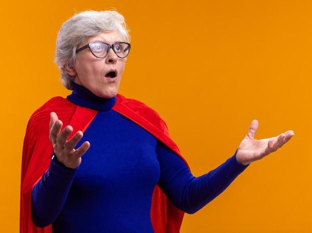 Starsza kobieta superbohaterka w okularach w czerwonej pelerynie patrząca na bok zdumiona i zaskoczona z podniesionymi rękami stojącymi nad pomarańczowym tłem