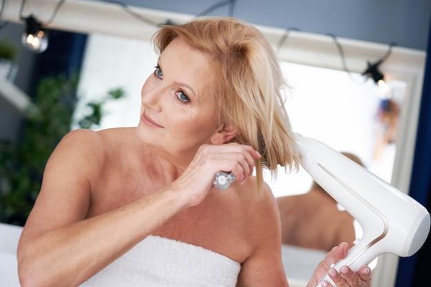 Starsza kobieta susząca włosy w łazience