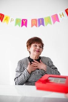 Starsza kobieta świętuje jej birthay w domu z tortem, ballons i confetti
