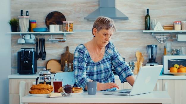 Starsza kobieta szuka przepis online za pomocą laptopa w kuchni podczas śniadania. osoba w podeszłym wieku na emeryturze pracująca w domu, pracująca zdalnie przy użyciu zdalnej komunikacji internetowej, praca online w nowoczesnym technologi